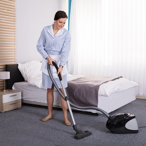 Woman vacuuming Carpet in bedroom | Custom Floors
